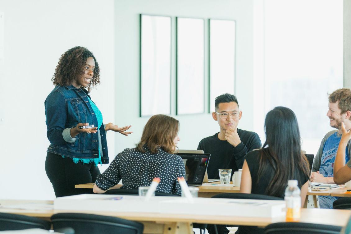 Imagem de uma mulher afrodescendente em pé explicando algo para outras cinco pessoas que estão sentadas ao redor de uma mesa de trabalho
