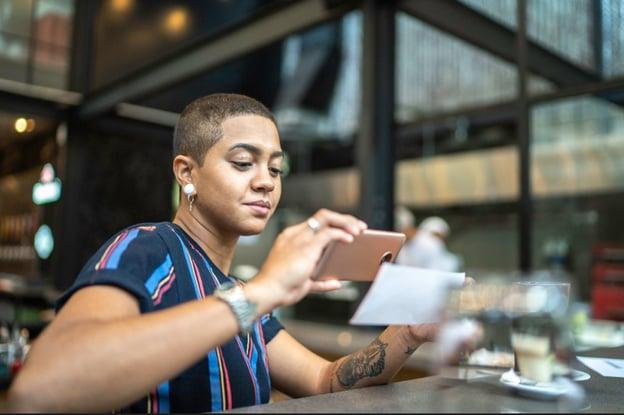 Imagem de uma mulher tirando foto de um documento, representando a admissão digital
