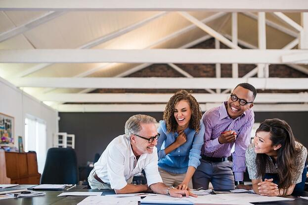 4 pessoas no ambiente de trabalho sorrindo ao redor de uma mesa