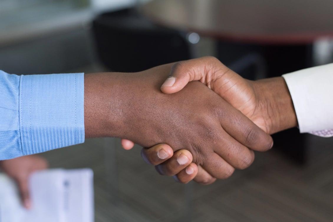Dois homens negros apertando as mãos, representando a aquisição de talentos