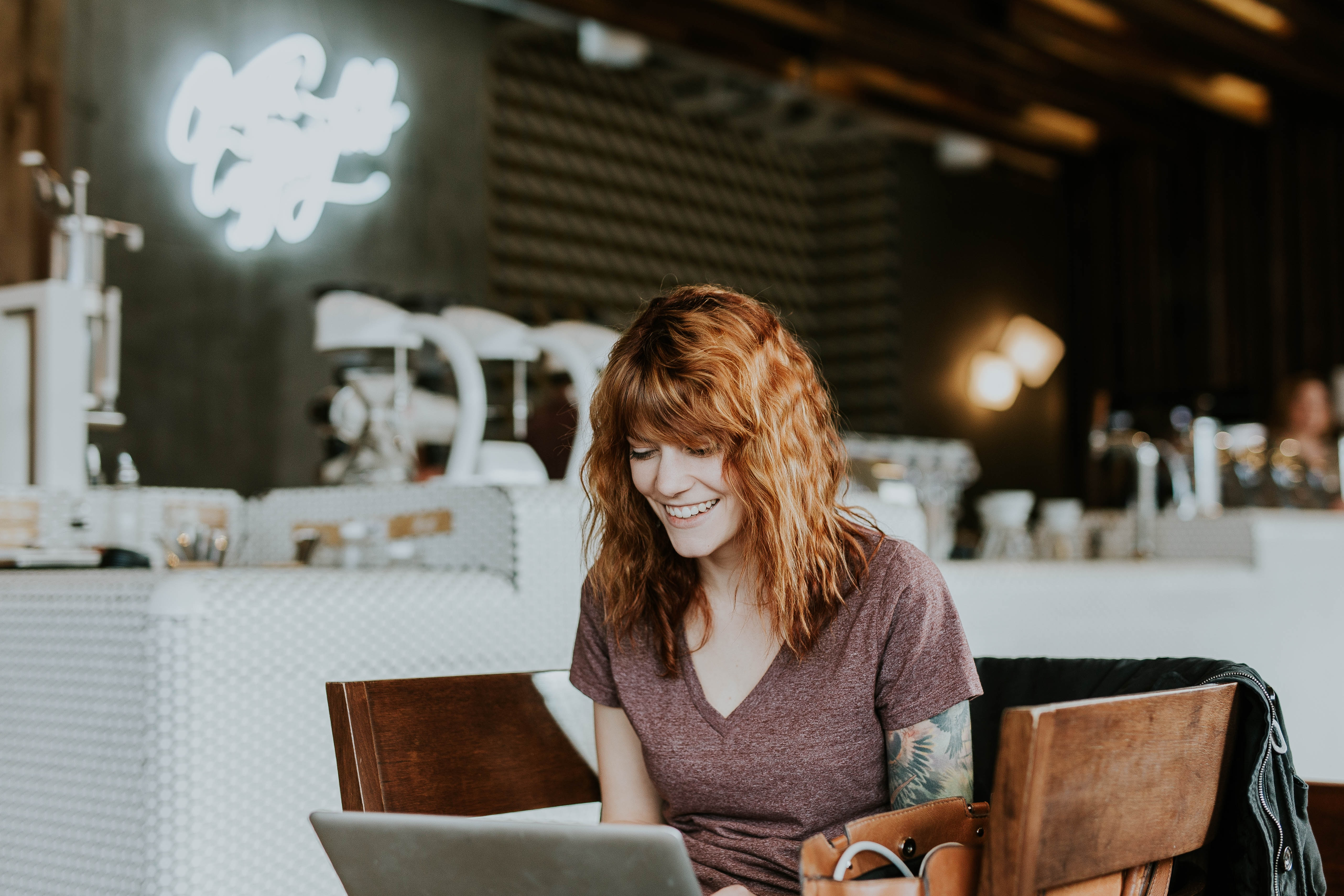 Mulher sentada e sorrindo olhando para o notebook