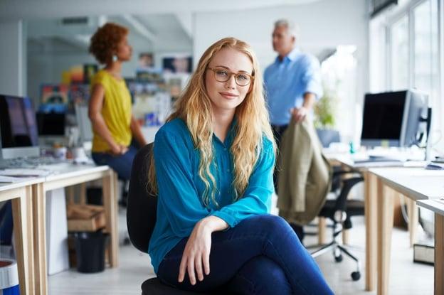 Mulher com óculos, camisa azul, cabelo longo, sentada de pernas cruzadas
