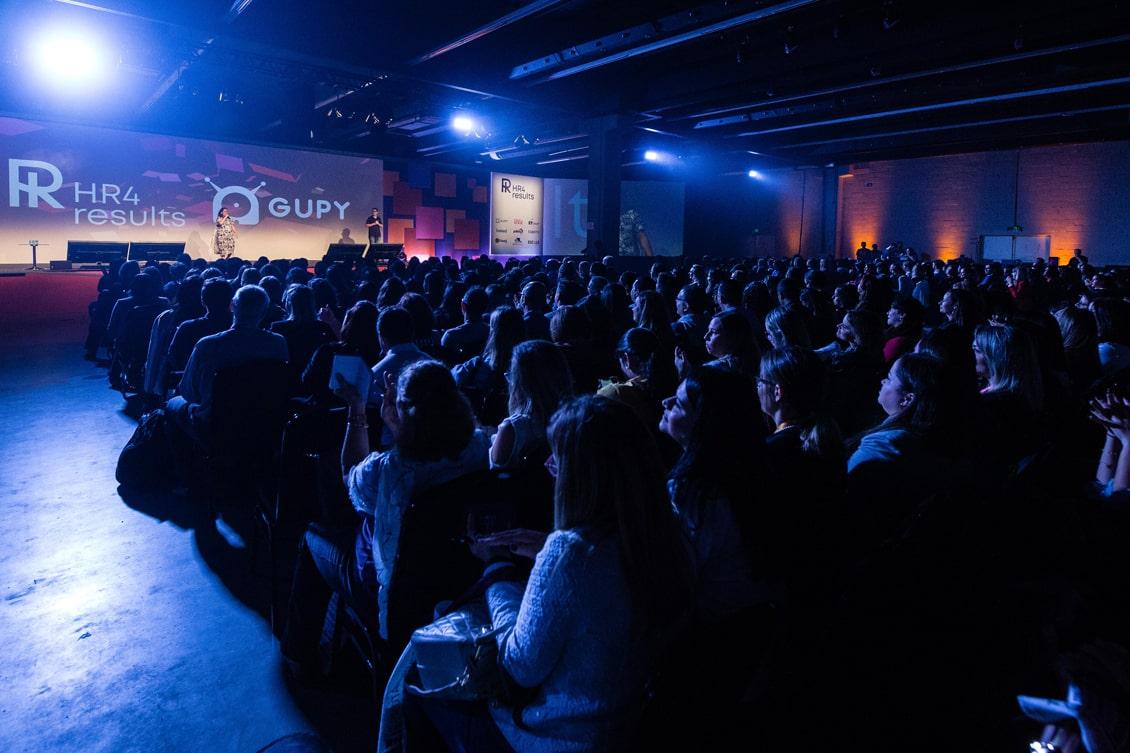 Imagem de um palco com palestrante e participantes, representando os eventos de rh 2020