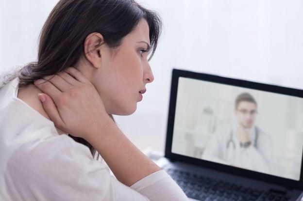 Mulher com mão no pescoço em uma consulta médica on-line