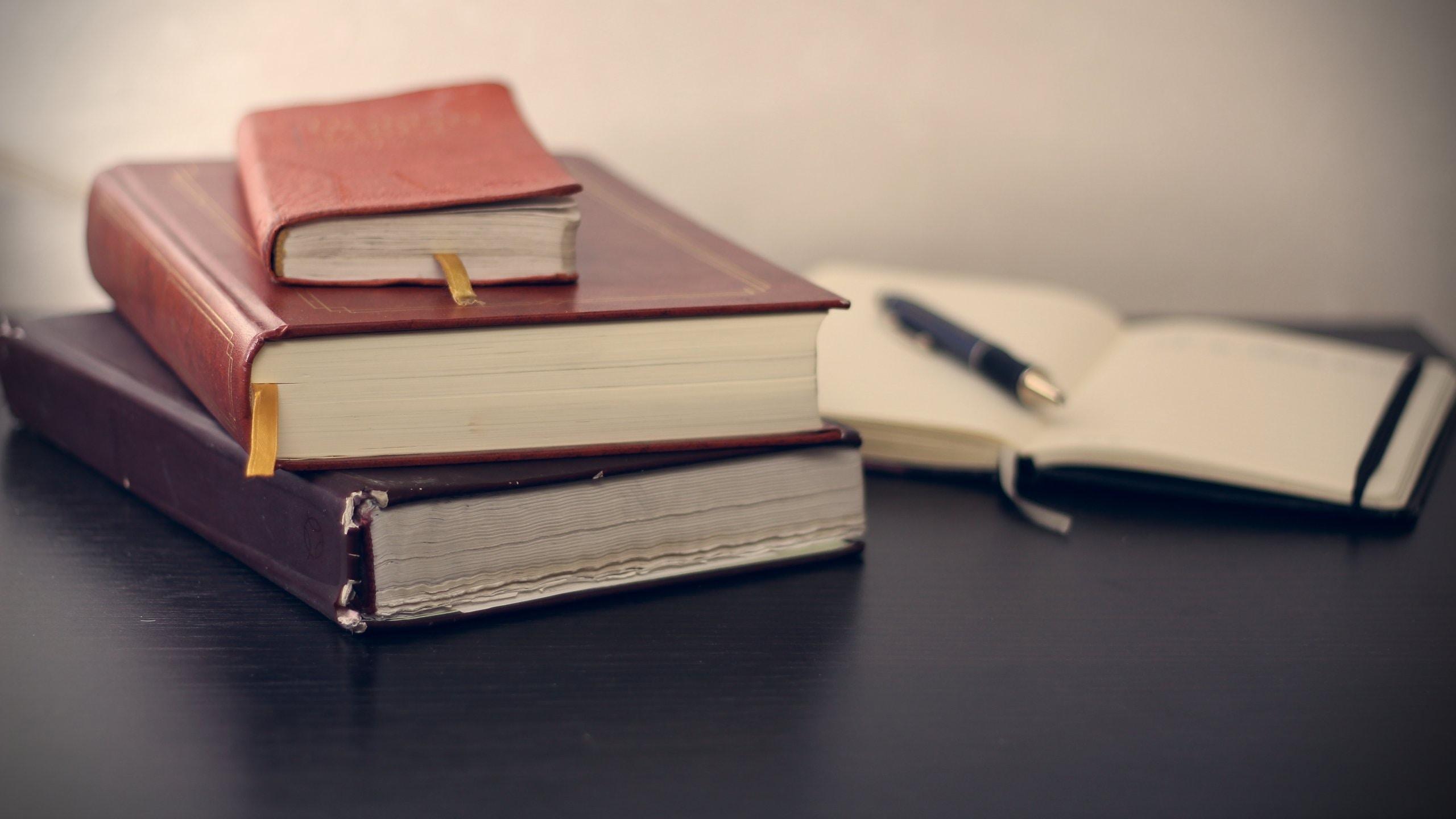 Três livros empilhados sobre a mesa e, ao fundo e desfocado, um caderno aberto com uma caneta sobre ele