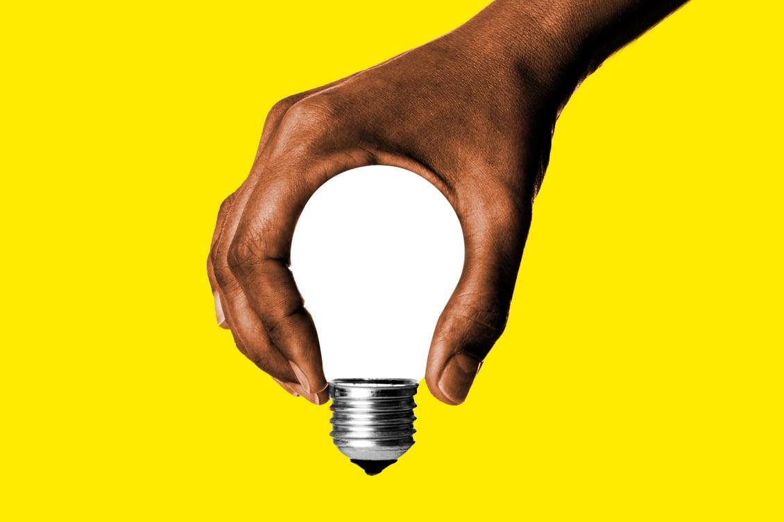 Imagem de uma mão segurando uma lâmpada, simbolizando a junção entre marketing e RH