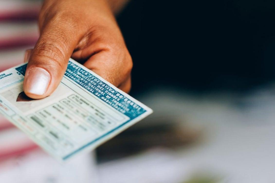 Imagem de uma pessoa segurando um documento, representando os modelos e fichas da admissão de colaboradores