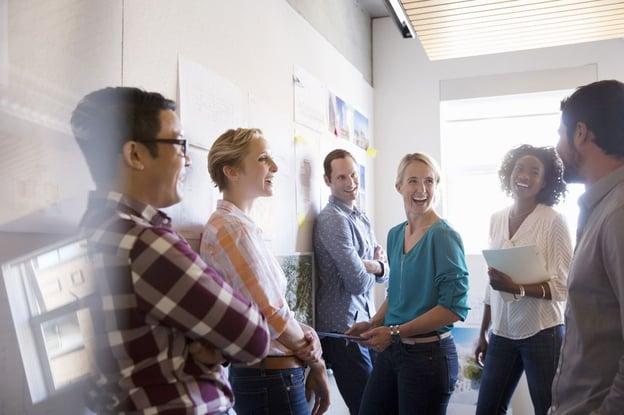 Seis trabalhadores em pé sorrindo e conversando