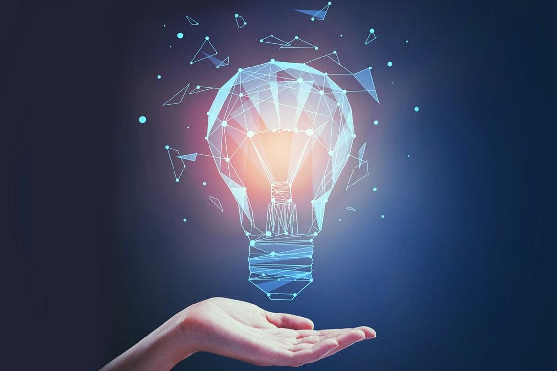 A imagem mostra uma mão com a palma para cima sobre a qual está uma lâmpada com design futurista desenhada.