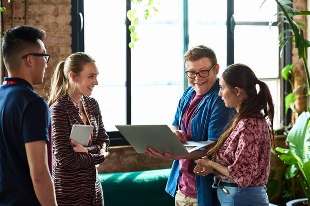 Quatro pessoas com um notebook executando uma pesquisa de clima organizacional