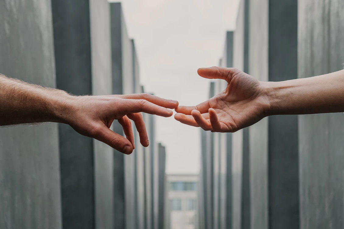 Imagem de duas mãos se tocando, representando um programa de indicação
