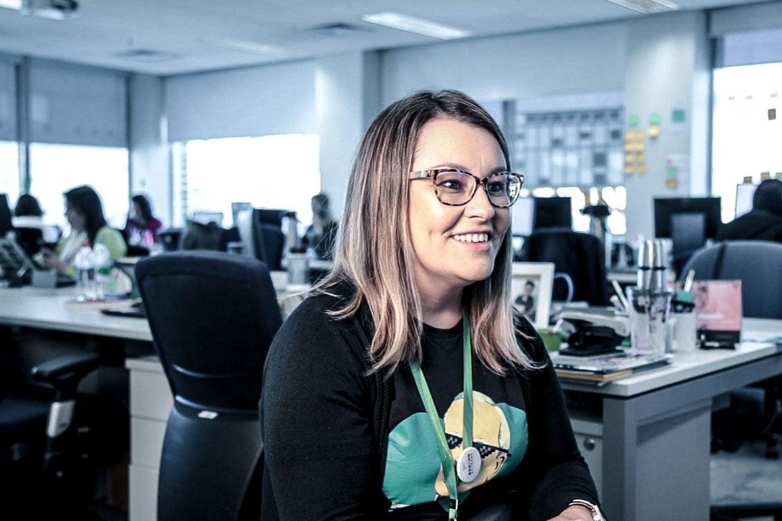 Alexandra Godoy aparece sorrindo no escritório da Sicredi representando o RH estratégico.