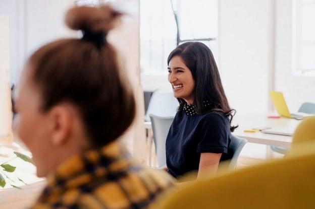 Mulher trabalhando feliz, representando saúde mental dos colaboradores