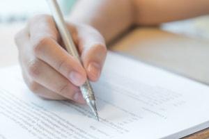 a mão de uma pessoa escrevendo em uma prova