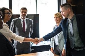 duas pessoas dão um aperto de mãos representando um acordo fechado, enquanto outras pessoas presentes na reunião observam alegres com o novo acordo