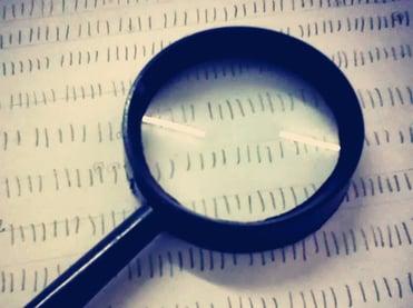 Imagem de uma lupa em cima de um papel contendo o teste palográfico