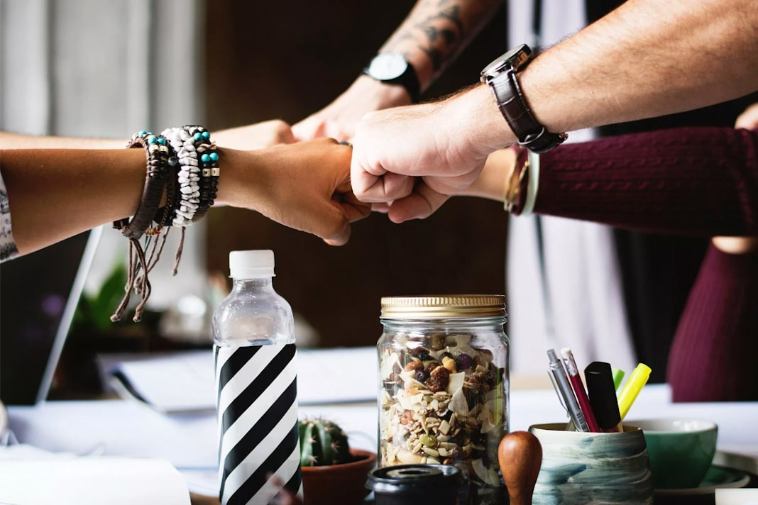 funcionários com as mãos unidas representando a gestão de pessoas