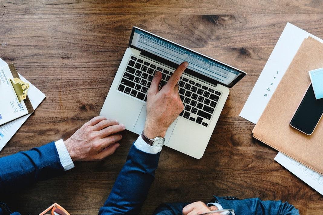 Mãos de uma pessoa fazendo um processo de recrutamento e seleção em seu notebook, que está em cima de uma mesa de madeira, com outros papéis e um celular ao lado